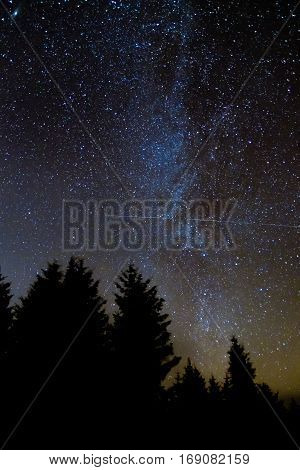 International Space Station passing in front of Milky Way. Relatively clear view of the galaxy with coniferous forest silhouette in foreground in Brecon Beacons National Park Wales UK