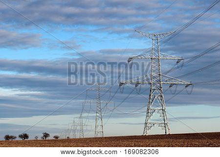 high voltage electric transmission pylon on agriculture field