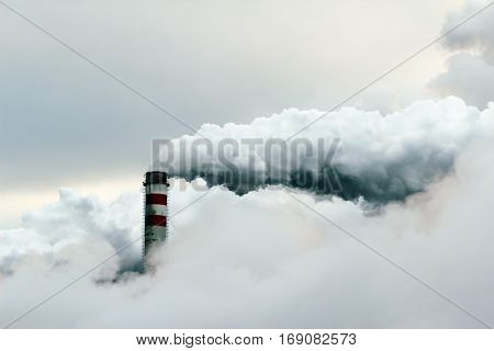 big cloud of smoke coming out of power plant chimney pollution air