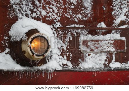 front view details of a red old train locomotive covered in snow frost and icicles in railway station winter time