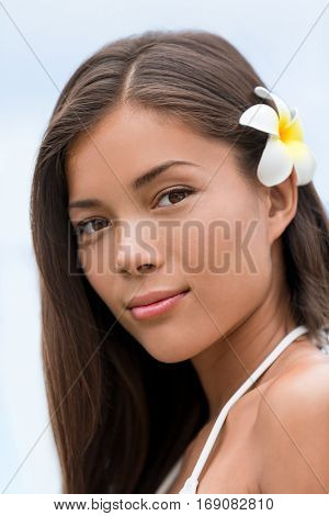 Asian beauty young woman hawaiian flower portrait. Wellness skincare treatment concept. Serene multicultural girl outdoors at tropical spa. Young mixed race model on Hawaii.