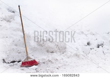 front view of a red house broom in front of snow gathered in a pile in winter