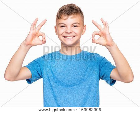Half-length emotional portrait of caucasian teen boy wearing blue t-shirt. Funny teenager making ok gesture, isolated on white background. Handsome child laughing looking very happy.