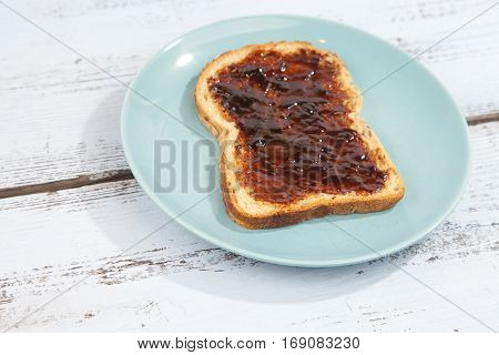 Typical Dutch apple syrup called Appelstroop on bread on wooden background