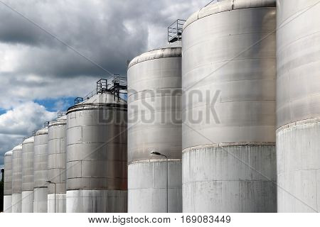 large stainless steel fermentation vessel under cloudy sky