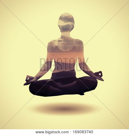 Yoga concept. The image is created using the multiple exposures. Image of a silhouette of a young woman soaring in the lotus position and mountain landscape at sunrise