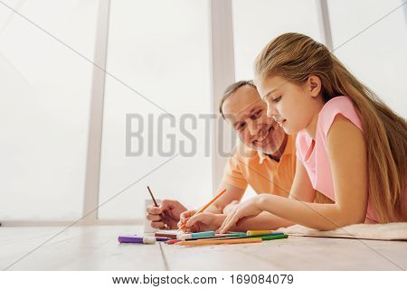 Joyful girl and grandfather are painting together by felt-tip pens. They are lying on flooring and laughing