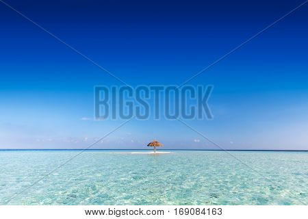 Tropical sandbank island with sunshade umbrella. Indian Ocean, Maldives. Blue clear sky