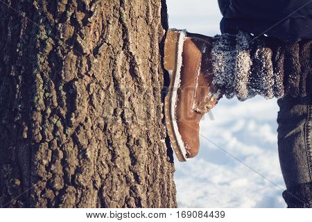 horizontal close up of woman with brown boots textile gaiters and blue jeans leaning against a large tree covered in snow in winter time concept for hiking