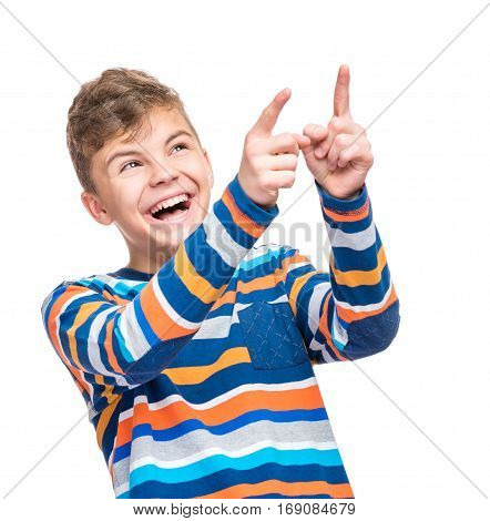 Emotional portrait of caucasian teen boy. Funny teenager pointing and looking upwards while laughing, isolated on white background. Handsome happy child pointing at copy space.
