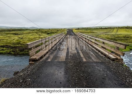 wooden bridge across the wild icelandic river Iceland view at Iceland green plains during summertime