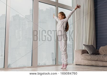 Good morning. Sleepy girl is standing near window and stretching arms up. She is smiling happily