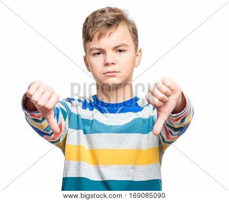 Close up emotional portrait of caucasian unhappy teen boy giving thumbs down hand gesture. Angry child looking with disapproval facial expression, isolated on white background. Negative human face expressions - body language.