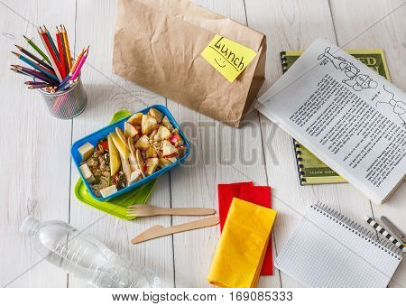 Healthy school lunch for child or teenager, top view, flat lay background. Pile of exercise books, water, bag and food in lunch box on white wood table, cracker with cheese and apples