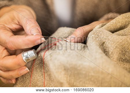 Close-up partial view of woman sewing cloth with needle and red thread