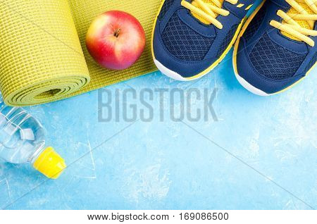 Yoga mat sport shoes apples bottle of water on dark background. Concept healthy lifestyle healthy food sport and diet. Sport equipment. Copy space