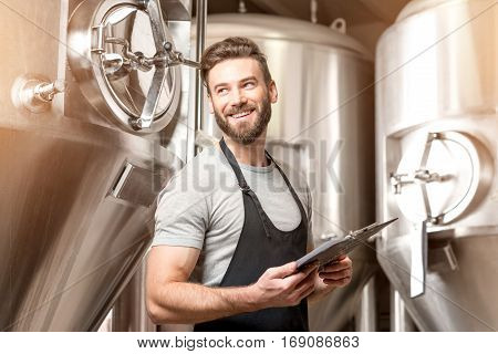 Brewer supervising the process of beer fermentation at the manufacturing with metal containers on the background