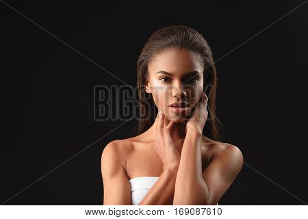 Voluptuous young african girl is touching her face and looking at camera with passion. Isolated on black background. Copy space in left side