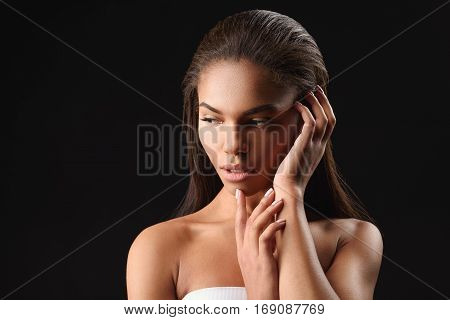 Waist up portrait of passionate mulatto woman standing and touching her smooth skin with satisfaction. Isolated and copy space in left side