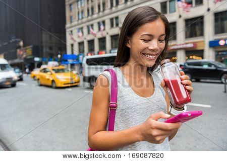Urban city modern Asian girl using phone app drinking healthy fruit vegetable juice smoothie walking on Manhattan street New York city, USA. Happy young adult health lifestyle.