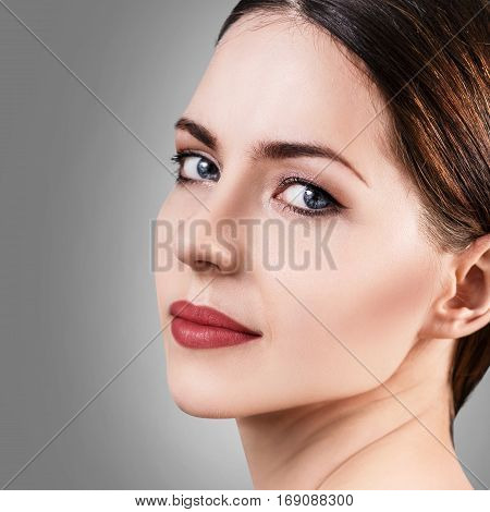 Beautiful woman with healty fresh skin looking around over gray background. Spa concept.