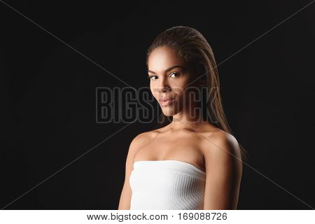 Seductive young mulatto girl is posing with confidence. Isolated and copy space in left side