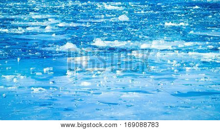 Blue frozen river with small floes in winter