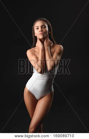 Seductive young african woman is standing and posing in tight underwear. She is touching her neck and looking forward with desire. Isolated