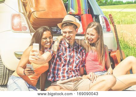 Happy friends making selfie photo standing next car full of suitcases and bags - Young people having fun in road trip holidays - Traveling and friendship holidays concept - Warm cinematic filter