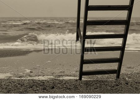 Metal ladder with wooden steps to sea after rain