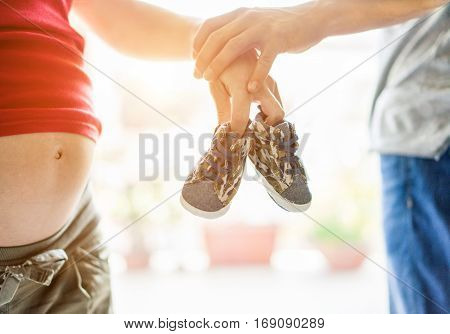 Father holding pregnant mother hand with baby shoes with bright background - Young people waiting for son - Family and happy future together concept - Focus on shoes - Warm filter with back sun light
