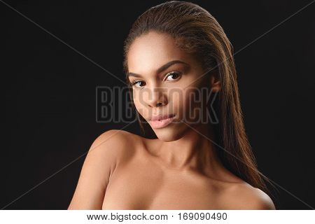 Attractive nude mulatto girl is posing and looking at camera with confidence. Isolated