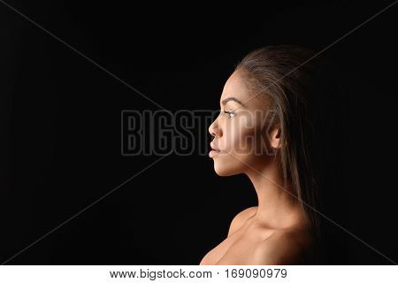 Sexy young nude mulatto woman is standing in profile. She is looking forward with confidence. Isolated and copy space in left side