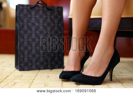 Woman buying new shoes. Closeup female feet wearing black suede high heels next to shopping bag, girl trying on her new fashion sexy footwear. At home or store.