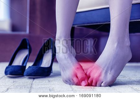 Medical concept. Foot pain. Body health problem, healthy feet swollen joints or blisters, wounds on skin. Painful barefoot woman at home or office with high heels in the background