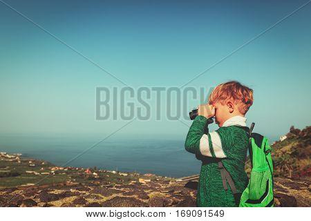 little boy looking through binocular on travel in nature, kids travel