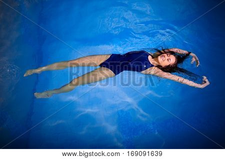 Young woman swimmer in blue pool water