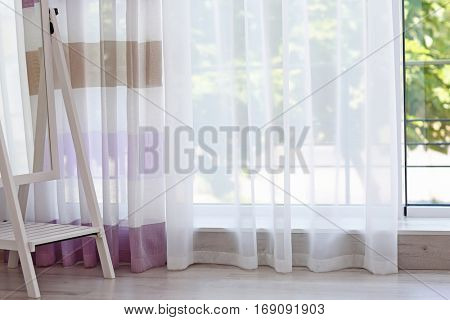 Mirror near room window with colorful striped curtains