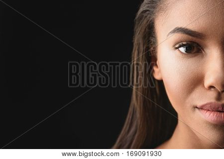 Close up of half of female face. Beautiful african woman is looking at camera with confidence. Isolated and copy space in left side