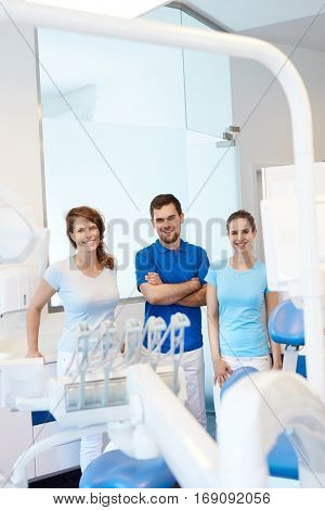 Team photo of dental surgeon and assistants in dentist's office, smiling, looking at camera.
