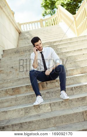 Young man sitting on stairs, talking on mobilephone outdoors.