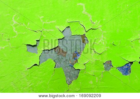 Peeling paint of green and blue colors on the stone texture background with green peeling paint. Peeling paint texture surface of green color. Texture background. Texture surface