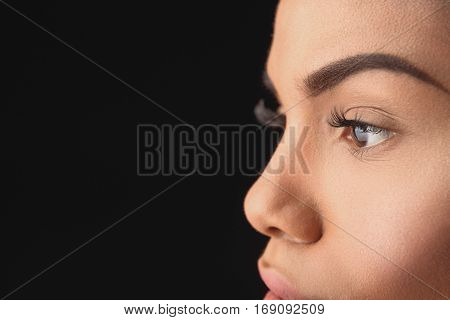 Close up of charming female eyes in profile. African young woman is looking straight with confidence. Isolated and copy space in left side