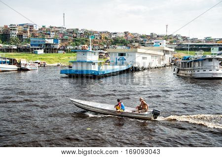 Manaus Brazil-December 04 2015: two men on motor boat floating on water in old harbour with dock and many houses outdoor