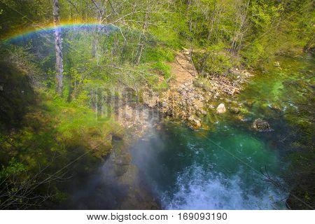 Rainbow over mountain stream flowing through gorge. Vintgar Gorge near Bled, Triglav National park, Slovenia