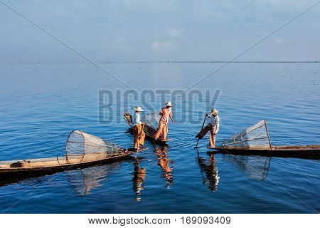 Myanmar travel attraction landmark - three traditional Burmese fishermen with fishing nets on boats at Inle lake in Myanmar famous for their distinctive one legged rowing style