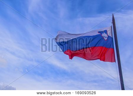 Slovenian national official flag on flagpole waving in the wind on picturesque blue sky background