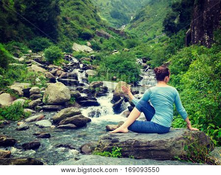 Yoga exercise outdoors -  woman doing Ardha matsyendrasana asana - half spinal twist pose at tropical waterfall in Himalayas in India. Vintage retro effect filtered hipster style image.