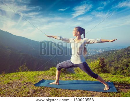 Yoga outdoors - sporty fit woman doing yoga asana Virabhadrasana 2 - Warrior pose posture outdoors in Himalayas mountains in the morning. Vintage retro effect filtered hipster style image.