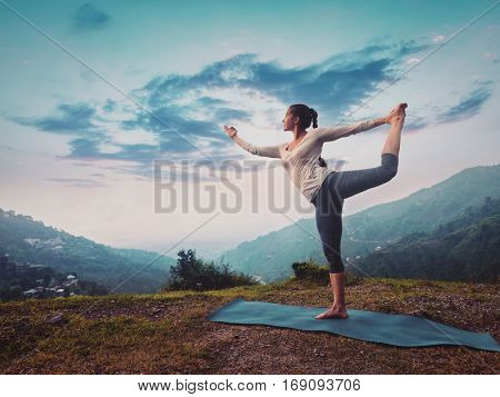 Woman doing yoga asana Natarajasana - Lord of the dance pose outdoors on sunset in Himalayas. Vintage retro effect filtered hipster style image.